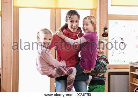 Female educator rampaging with three kids in kindergarten - Stock Photo