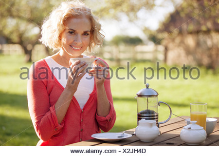 A mature woman sitting at a garden bench drinking coffee - Stock Photo