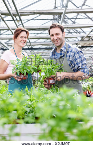 Germany, Bavaria, Munich, Mature man and woman in greenhouse with rocket plant, smiling, portrait - Stock Photo