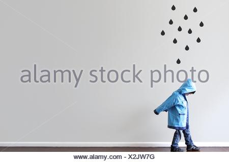 Boy in raincoat walking past a wall with black raindrops painted on the wall - Stock Photo