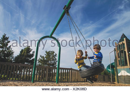 Two young boys swinging on a tire swing at a park - Stock Photo