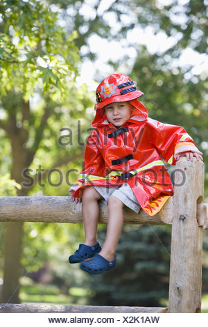 A young boy in a firefighter costume sitting on a fence - Stock Photo