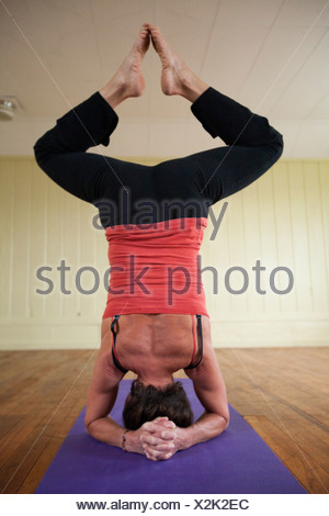 An older woman performs a more advanced technique of yoga in a small studio. - Stock Photo