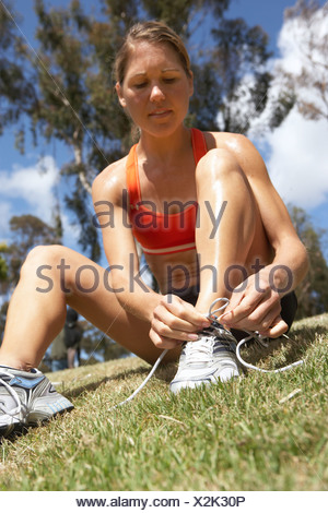 Woman tying trainer shoelace in park sitting on grass close up surface level tilt - Stock Photo