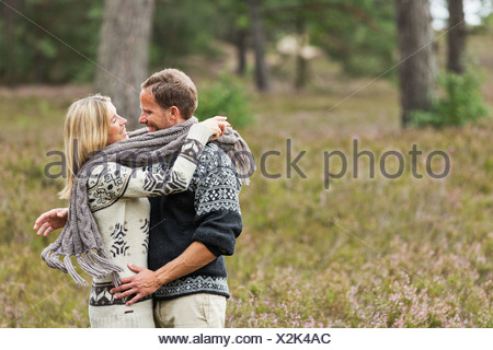 Mid adult couple wrapped in scarf hugging - Stock Photo