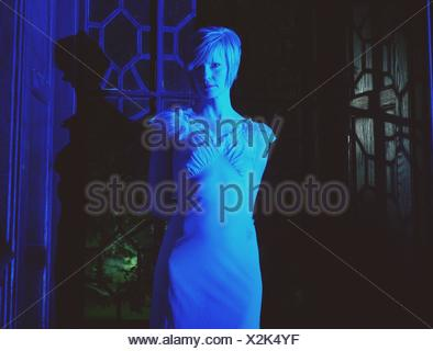 Portrait Of Beautiful Young Woman In Lit Room - Stock Photo