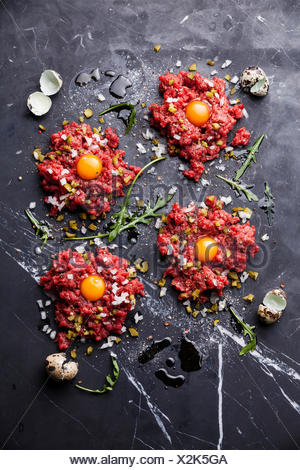 Beef tartare with pickled cucumber and fresh onion on dark marble background - Stock Photo