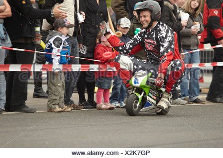 Motorcycle stuntman Mike Auffenberg riding a pocket bike, Koblenz, Rhineland-Palatinate, Germany, Europe - Stock Photo