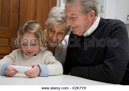 A grandson using a electronic device while his grandparents watch - Stock Photo
