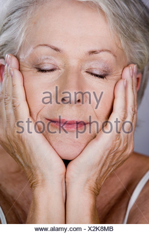 A senior woman with head resting in hands - Stock Photo