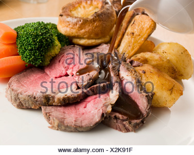 Gravy being Poured on a plate of Roast Beef and Yorkshire Pudding - Stock Photo