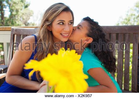 Girl kissing her mothers cheek on garden bench - Stock Photo