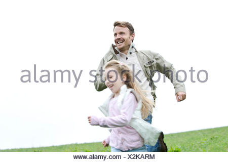Happy father and daughter running in meadow - Stock Photo
