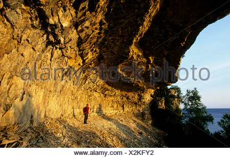 A hiker enjoys the view under Overhanging Point, Bruce Peninsula National Park, Ontario, Canada. - Stock Photo