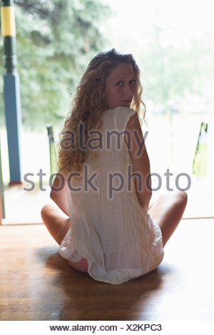 Teenage girl sitting at front door - Stock Photo