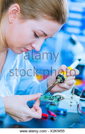 MODEL RELEASED. Young woman soldering a printed circuit board. - Stock Photo