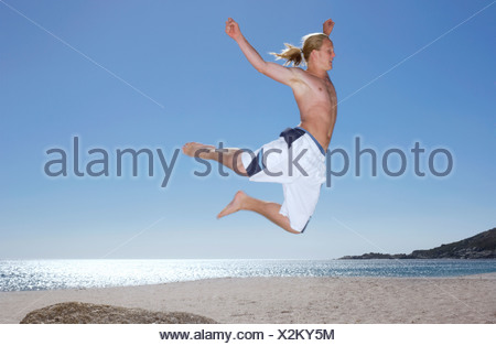 Teenage boy 17 19 in white swimming shorts leaping from rock on beach side view - Stock Photo