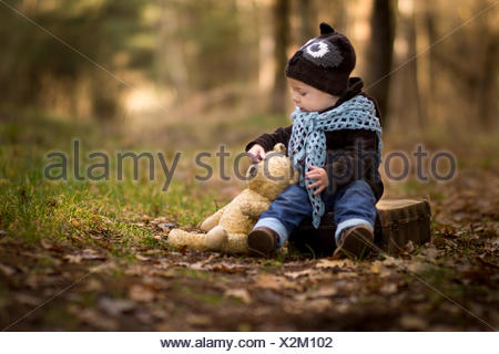 Portrait of baby boy sitting in forest with his teddy bear - Stock Photo