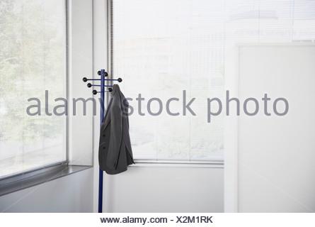 office coat rack. Suit Jacket Hanging On Office Coat Rack - Stock Photo G