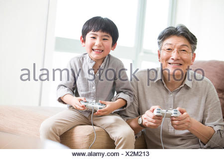 Cheerful grandfather and grandson playing video game - Stock Photo