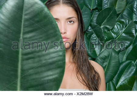 Woman hiding behind a leaf - Stock Photo