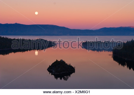 The full moon rising over Emerald Bay at sunset with ...