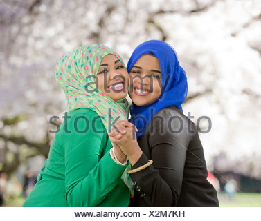 Portrait of two young females in park dancing together - Stock Photo