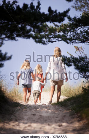 Sweden, Gotland, Faro, Skar, Mother with son (2-3) and daughters (8-9, 10-11) walking along footpath - Stock Photo