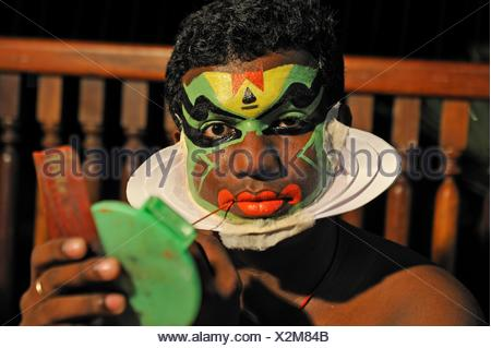Kathakali performer during making up before a show at the Kumarakom Lake Resort hotel, Kerala state, South India, Asia. - Stock Photo