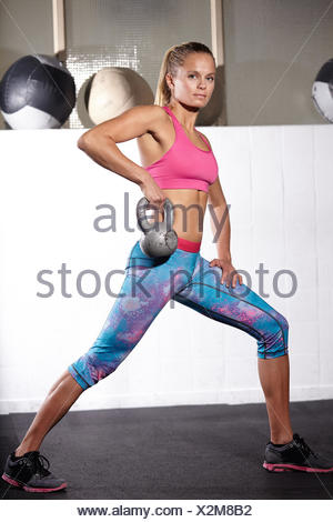 Young woman lifting kettle bell in gym - Stock Photo