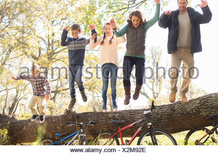 Enthusiastic family jumping from fallen log over bicycles - Stock Photo
