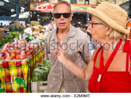 Older mature senior couple looking at fruits and vegetable stand in an outdoor market in Martinique. They are choosing carefully their grocery. - Stock Photo