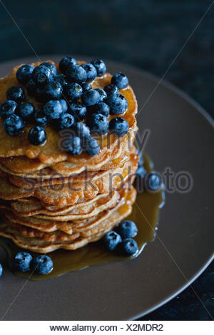 Stack of Apple spelt pancakes topped with maple syrup and fresh blueberries - Stock Photo