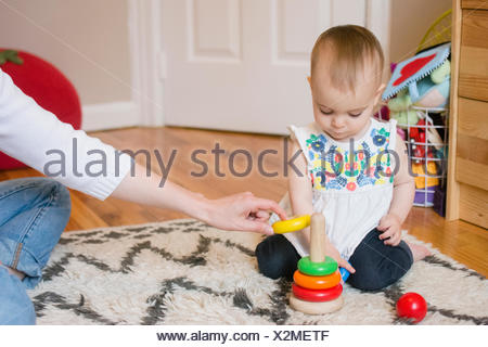 Baby girl (18-23 months) playing with mother - Stock Photo