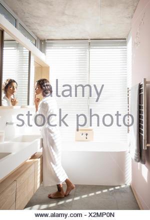 Woman in bathrobe examining face in bathroom mirror - Stock Photo