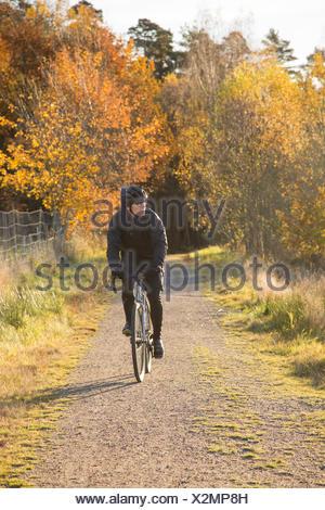 Sweden, Vastergotland, Lerum, Mature man riding bicycle on dirt road through autumn forest - Stock Photo