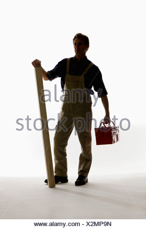 A construction worker holding a toolbox and plank - Stock Photo