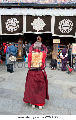 Tibetan Buddhist, monk praying in front of the Jokhang Temple, Barkhor Square, Lhasa, Himalayas, Tibet, China, Asia - Stock Photo
