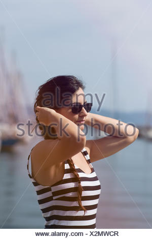 Portrait of a young woman holding her hands to her ears - Stock Photo
