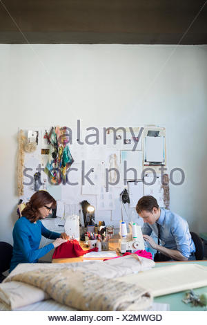 Dressmakers using sewing machines at workbench - Stock Photo