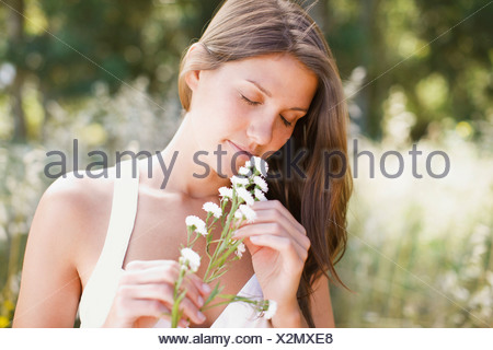 Serene woman smelling flowers outdoors - Stock Photo