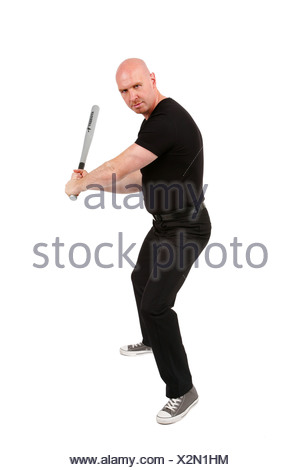 bald headed man with baseball bat in his hands is looking angry into the camera - Stock Photo