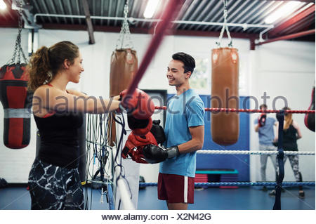 Female boxer leaning on boxing ring ropes talking to male boxer - Stock Photo