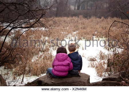 Boy and girl sitting on rock in forest, Sofia, Bulgaria - Stock Photo