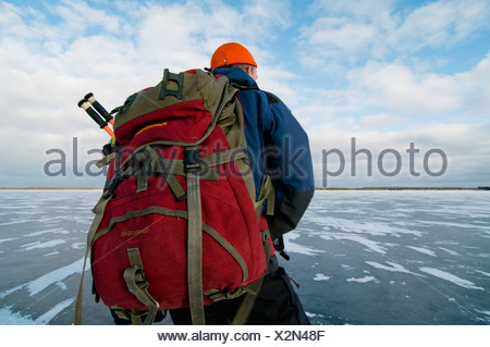 Man with backpack on ice - Stock Photo
