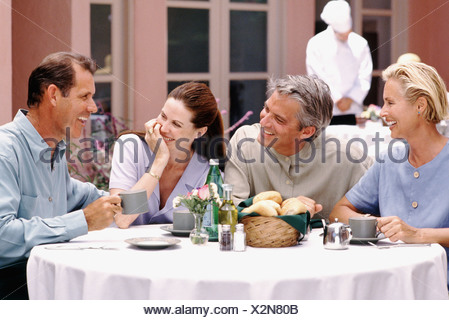 Two couples having dinner together on patio of restaurant - Stock Photo
