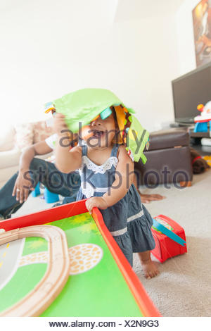 Baby girl playing, father in background - Stock Photo