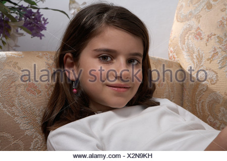 Girl (9-11) lying on sofa, portrait - Stock Photo