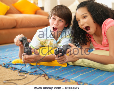 Teenage girl and boy playing video games - Stock Photo