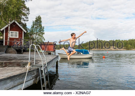 Boy jumping from jetty - Stock Photo